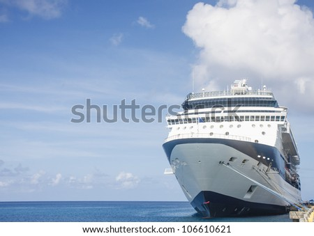 A blue and white luxury cruise ship tied up to a pier under nice sky - stock photo