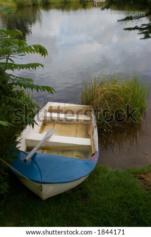 A blue and white rowboat on the shore of a pond, surrounded by nature.