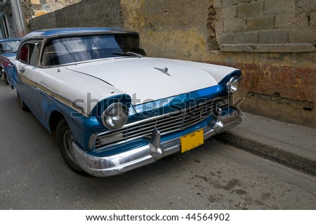 A blue and white 1950s American car still running on the streets of Cuba.