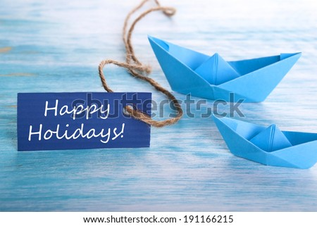 A Blue Banner with Happy Holidays and Boats - stock photo