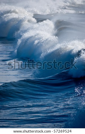 A blue beach breaker in early morning light - stock photo