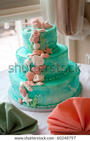 A blue beach themed wedding cake with three tiers. - stock photo