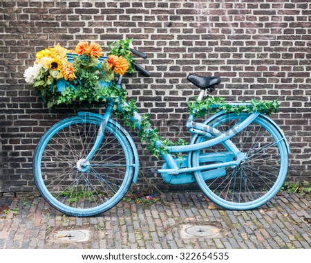 A blue bike decorated with flowers is parked against a brick wall in Haarlem, The Netherlands.