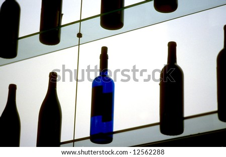 A blue bottle on a backlit bar shelf among black bottles - stock photo