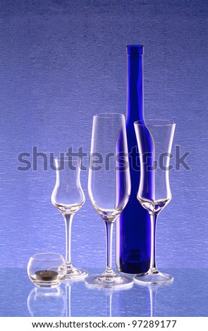 A blue bottle, three wineglasses and a candlestick - stock photo