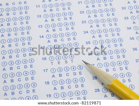 A blue bubble or scantron sheet with a number two yellow pencil.  The word Test stands out in the middle of the answer sheet. - stock photo