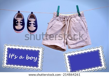 A blue card hanging on line with baby booties and shorts isolated on a blue background for you message, It is a Boy Announcement  - stock photo