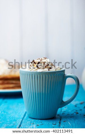 A blue ceramic cup of coffee or cocoa topped with whipped cream on a blue wooden table. Milk and dark chocolate on the top and around the cup. Vertical image with copyspace - stock photo