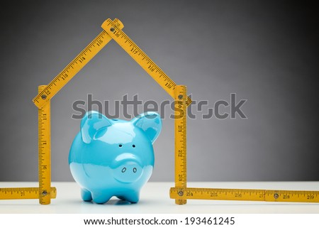 A blue ceramic piggy bank under a measurement tape in the shape of a new house - concept about construction and finances or savings. - stock photo