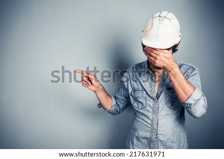 A blue collar worker covering his face is pointing - stock photo
