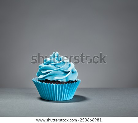 A Blue Cupcake on a grey background - stock photo