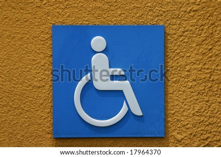 A blue disabled access sign on painted orange concrete wall. - stock photo