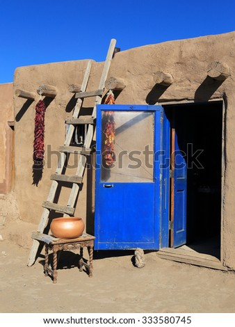 A blue door and wooden ladder are typical sights at the Taos pueblo in New Mexico. - stock photo
