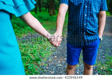 a blue dressed couple walking together by their hands on a rocky forest path
