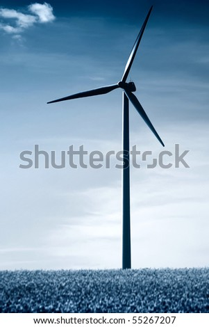 A blue duo-toned windmill in a rapeseed field - stock photo