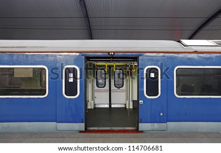 A blue electric train carriage with an open sliding mechanical door at a train station platform. - stock photo