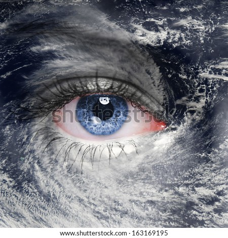 A blue eye in the middle of a tropical hurricane. Elements of this image furnished by NASA - stock photo