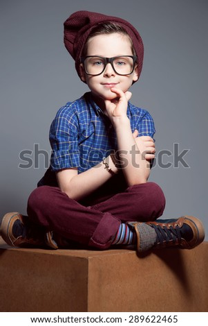 A blue - eyed kid with glasses. A boy is sitting with so merry face. He is wearing plaid shirt and burgundy pants with hat - stock photo