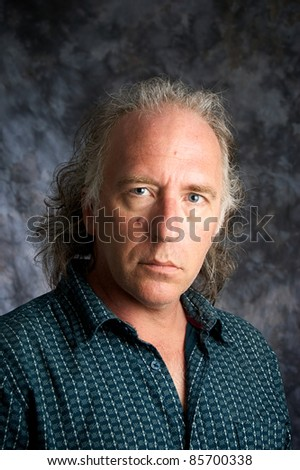 A blue eyed mature white american male wearing casual dress shirt looking at viewer. - stock photo