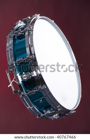 A blue finish snare drum isolated against a dark red background in the vertical format. - stock photo