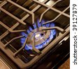 A blue flame from a gas cooktop burner - stock photo