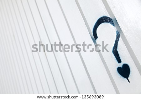 A blue graffiti in the shape of a question mark with a small heart instead of the dot, on a white metal wall with creases pattern. - stock photo