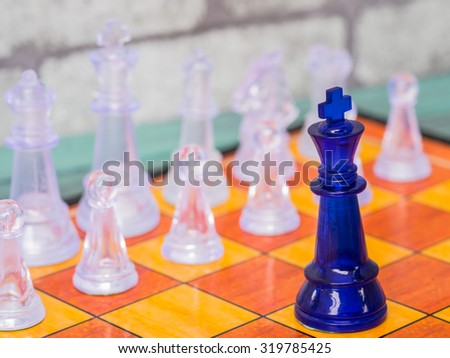 A blue king on the chess board confronting with a number of transparent glass chess pieces. - Business competition and leadership concept. - stock photo
