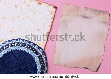 A blue kippah and matzah laying next to an old piece of paper. Add your text to the paper.