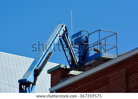 A blue lift bucket is raised to the roof of a brick building with tin roof. - stock photo