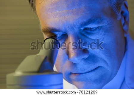 A blue light covers the face of a man who may be a scientist or doctor looking into a microscope. Blue gel used to create affect.
