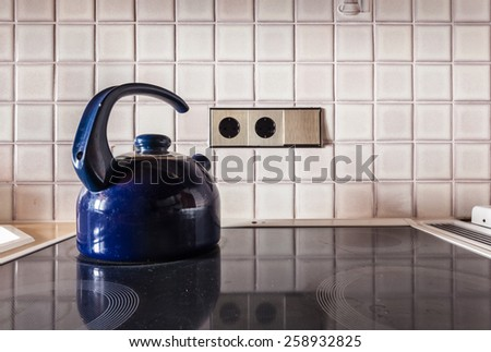 a blue metal kettle on the cooker of an electric stove in a kitchen - stock photo