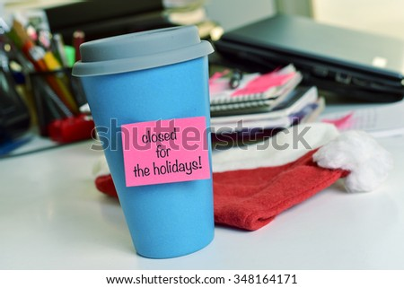 a blue mug with a pink sticky note with the text text closed for the holidays on an office desk - stock photo