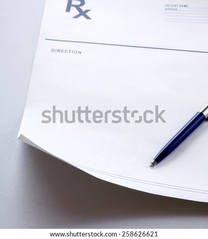 A blue pen on a rx prescription. - stock photo
