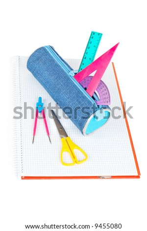 A blue pencil case with school supplies on a notebook - stock photo