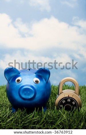 A blue piggy bank with a combination lock sitting on grass with a sky blue background, locking in your savings - stock photo