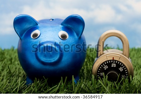 A blue piggy bank with a combination lock sitting on grass with a sky blue background, savings - stock photo