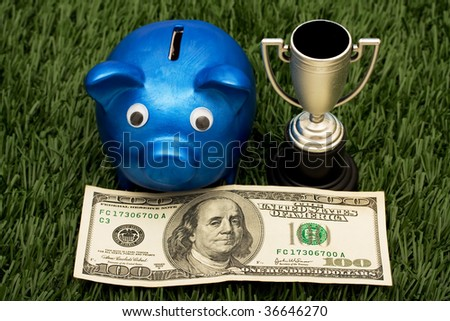 A blue piggy bank with a gold trophy sitting on grass background, winning with your savings - stock photo