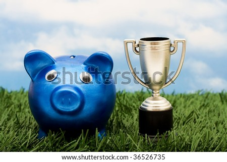 A blue piggy bank with a gold trophy sitting on grass with a sky blue background, winning with your savings - stock photo