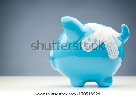 A blue piggy bank with a white bandage standing on a white surface with copy space in the background. - stock photo