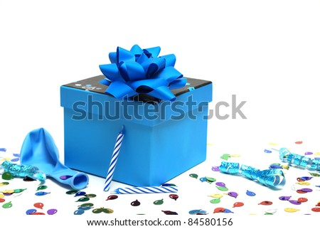 A blue present surrounded by various party supplies to enjoy the celebration. - stock photo