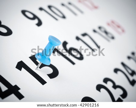 A blue push pin on the 15th day of a calendar. - stock photo