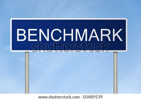 A blue road sign with white text saying Benchmark