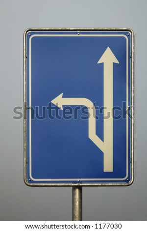 A blue roadsign indicating a fork in the road, but no place-names shown. The image was taken in evening light and the sign is set against a grey sky. Clipping path included. - stock photo