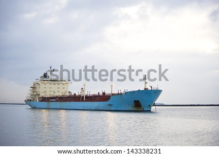 A blue shipping transportation freighter anchored just inside a port of call. - stock photo