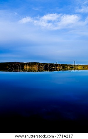 A blue sky reflecting in a calm northern lake - stock photo