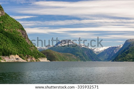 A blue sky with feather clouds over the banks of fjord with beautiful majestic mountains with green forest, Hardangerfjorden, Norway - stock photo