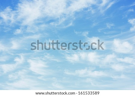 A blue sky with wisps of white clouds. - stock photo