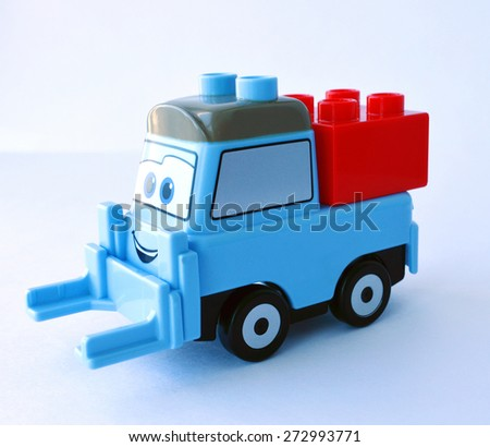 A blue smiling toy truck with a red squared constructor block on the white background - stock photo