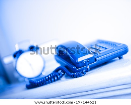 A blue telephone and an old alarm clock. - stock photo