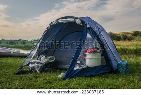 A blue tent at a peaceful campsite. - stock photo